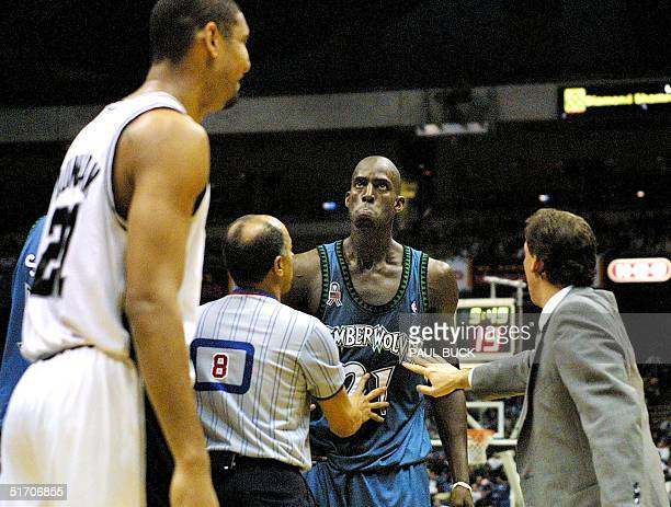 Kevin Garnett of the Minnesota Timberwolves has to be restrained by referree Luis Grillo and head coach Flip Saunders after he and Tim Duncan of the...