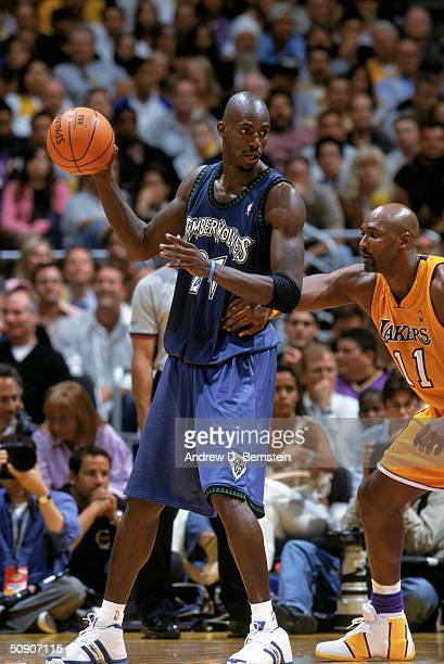 Kevin Garnett of the Minnesota Timberwolves looks to make a move while defended by Karl Malone of the Los Angeles Lakers in Game Three of the Western...