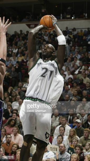 Kevin Garnett of the Minnesota Timberwolves puts the shot up over Darius Songaila of the Sacramento Kings on February 19 2004 at Target Center in...