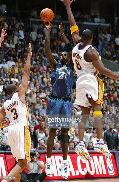 Kevin Garnett of the Minnesota Timberwolves shoots over Kobe Bryant and Devean George of the Los Angeles Lakers in Game four of the Western...