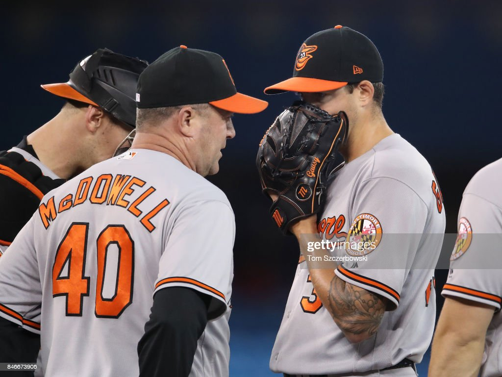 Kevin Gausman #39 of the Baltimore Orioles is visited on the mound by pitching coach Roger McDowell #40 in the seventh inning during MLB game action against the Toronto Blue Jays at Rogers Centre on September 13, 2017 in Toronto, Canada.