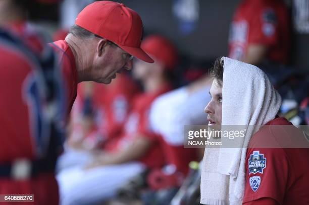Kevin Ginkel of University of Arizona talks with his coach on the bench against Coastal Carolina University during the Division I Men's Baseball...