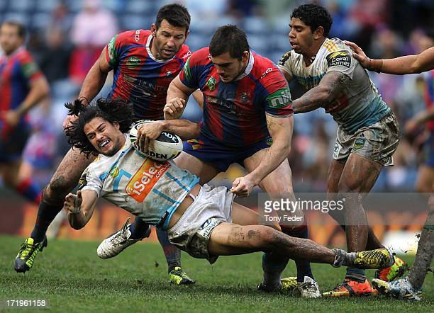 Kevin Gordon of the Titans about to be grabbed by the Knights defence during the round 16 NRL match between the Newcastle Knights and the Gold Coast...