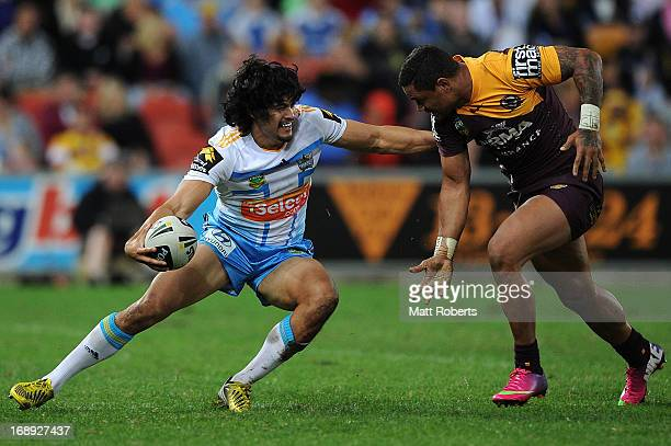 Kevin Gordon of the titans fends off the defence during the round 10 NRL match between the Brisbane Broncos and the Gold Coast Titans at Suncorp...