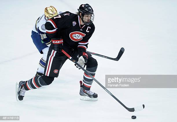 Kevin Gravel of the St Cloud State Huskies controls the puck against Peter Schneider of the Notre Dame Fighting Irish in overtime of the West...