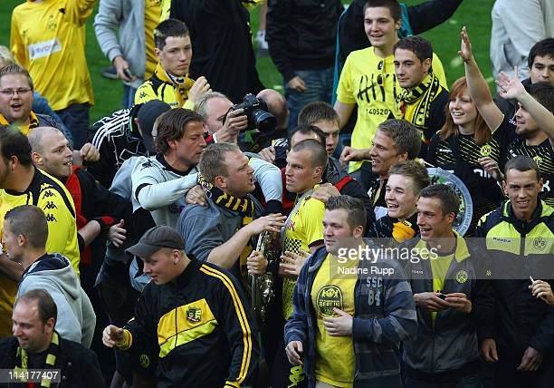 Kevin Grosskreutz of Dortmund is surrounded by fans who entered the pitch to celebrate with the trophy winning the German Championship after the...