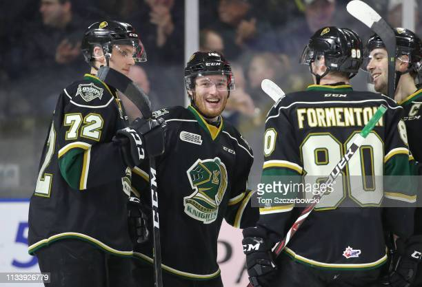 Kevin Hancock of the London Knights is congratulated after scoring a goal by Alec Regula and Alex Formenton and Evan Bouchard in the first period...