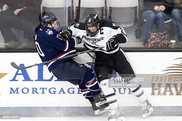 Kevin Hart of the Providence College Friars checks Brett Skibba of the Connecticut Huskies during NCAA hockey action at the Schneider Arena on...