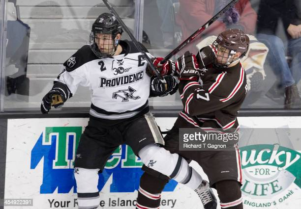 Kevin Hart of the Providence College Friars checks Zack Pryzbek of the Brown University Bears during NCAA hockey action at the Schneider Arena on...