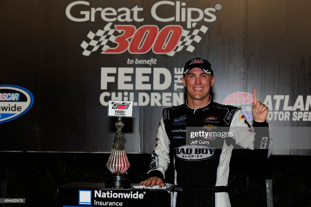 Kevin Harvick, driver of the #5 Bad Boy Buggies Chevrolet, poses with the trophy in Victory Lane after winning the NASCAR Nationwide Series Great Clips 300 at Atlanta Motor Speedway on August 30, 2014 in Hampton, Georgia.