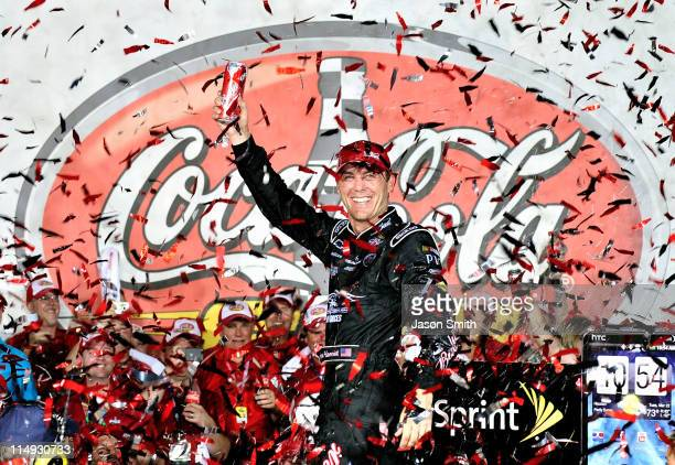 Kevin Harvick driver of the Budweiser Armed Forces Tribute Chevrolet celebrates in Victory Lane after winning the NASCAR Sprint Cup Series CocaCola...