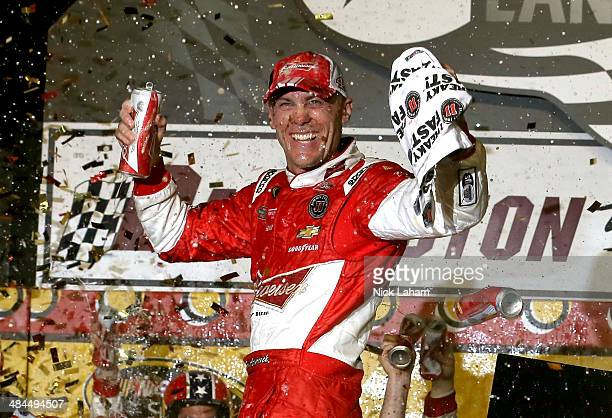 Kevin Harvick driver of the Budweiser Chevrolet celebrates in Victory Lane after winning the NASCAR Sprint Cup Series Bojangles' Southern 500 at...