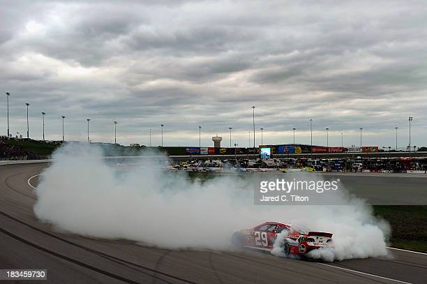 Kevin Harvick, driver of the Budweiser Chevrolet, celebrates with a burnout after winning during the NASCAR Sprint Cup Series 13th Annual Hollywood...