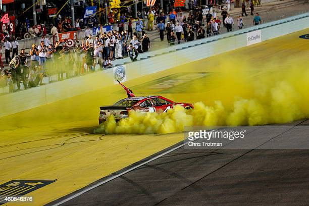 Kevin Harvick driver of the Budweiser Chevrolet celebrates with a burnout after winning during the NASCAR Sprint Cup Series Ford EcoBoost 400 at...
