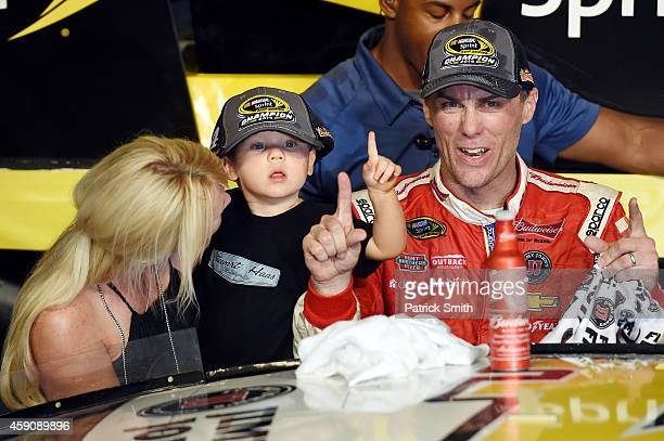 Kevin Harvick, driver of the Budweiser Chevrolet, celebrates with his wife DeLana and son Keelan in victory lane after winning during the NASCAR...