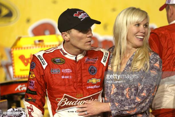 Kevin Harvick driver of the Budweiser Chevrolet celebrates with his wife DeLana in Victory Lane after winning the NASCAR Sprint Cup Series Bojangles'...