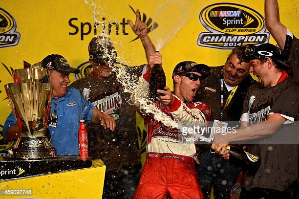 Kevin Harvick driver of the Budweiser Chevrolet celebrates with champagne in victory lane after winning the NASCAR Sprint Cup Series Ford EcoBoost...