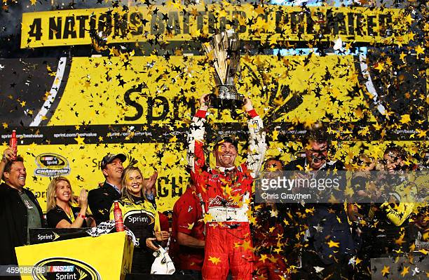 Kevin Harvick, driver of the Budweiser Chevrolet, celebrates with the trophy in victory lane after winning during the NASCAR Sprint Cup Series Ford...