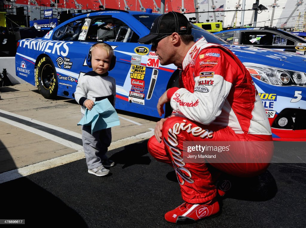 Kevin Harvick, driver of the #4 Budweiser Chevrolet, kneels with his son, Keelan Harvick, wipe off his car during practice for the NASCAR Sprint Cup Series Food City 500 at Bristol Motor Speedway on March 15, 2014 in Bristol, Tennessee.