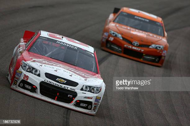 """Kevin Harvick, driver of the Budweiser Chevrolet, leads Matt Kenseth, driver of the Home Depot """"Let's Do This"""" Toyota, during the NASCAR Sprint Cup..."""