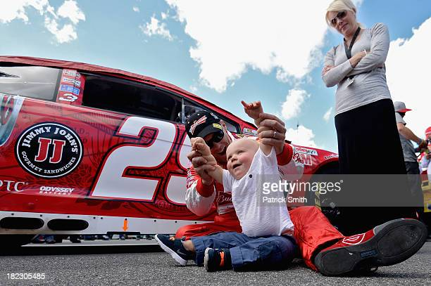 Kevin Harvick driver of the Budweiser Chevrolet plays with son Keelan and wife DeLana on the grid during prerace ceremonies for the NASCAR Sprint Cup...