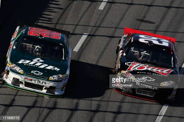 Kevin Harvick driver of the Budweiser Chevrolet race side by side Dale Earnhardt Jr driver of the Amp Energy/National Guard Chevrolet during the...