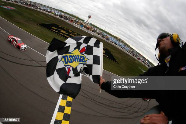 Kevin Harvick, driver of the Budweiser Chevrolet, races to the checkered flag to win the NASCAR Sprint Cup Series 13th Annual Hollywood Casino 400 at...