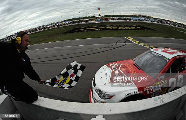 Kevin Harvick, driver of the Budweiser Chevrolet, retrieves the checkered flag after winning the NASCAR Sprint Cup Series 13th Annual Hollywood...
