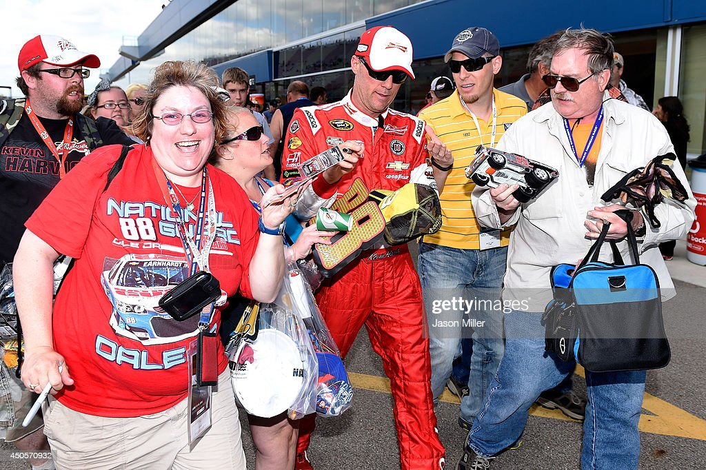 Kevin Harvick, driver of the #4 Budweiser Chevrolet, signs autographs for fans as he walks through the garage area during qualifying for the NASCAR Sprint Cup Series Quicken Loans 400 at Michigan International Speedway on June 13, 2014 in Brooklyn, Michigan.