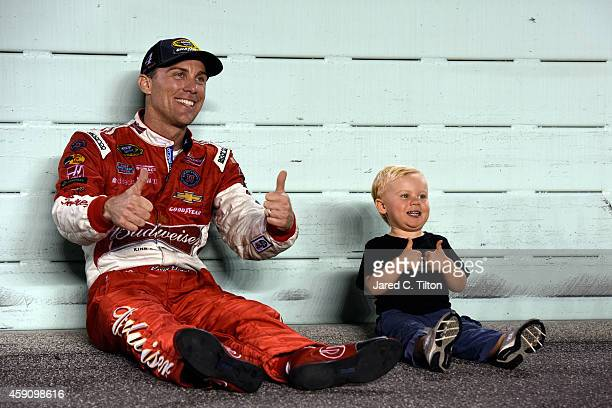 Kevin Harvick, driver of the Budweiser Chevrolet, sits with his son Keelan on the track after winning the NASCAR Sprint Cup Series championship and...