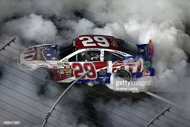 Kevin Harvick driver of the Budweiser Folds of Honor Chevrolet does a burnout after winning the NASCAR Sprint Cup Series CocaCola 600 at Charlotte...