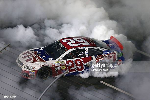 Kevin Harvick driver of the Budweiser Folds of Honor Chevrolet celebrates with a burnout after winning the NASCAR Sprint Cup Series CocaCola 600 at...