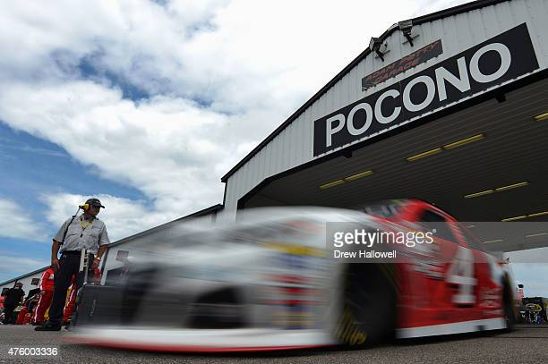 Kevin Harvick driver of the Budweiser/Jimmy John's Chevrolet drives through the garage area during practice for the NASCAR Sprint Cup Series Axalta...