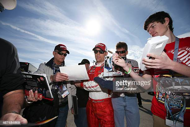 Kevin Harvick driver of the Budweiser/Jimmy John's Chevrolet signs autographs during practice for the NASCAR Sprint Cup Series 57th Annual Daytona...