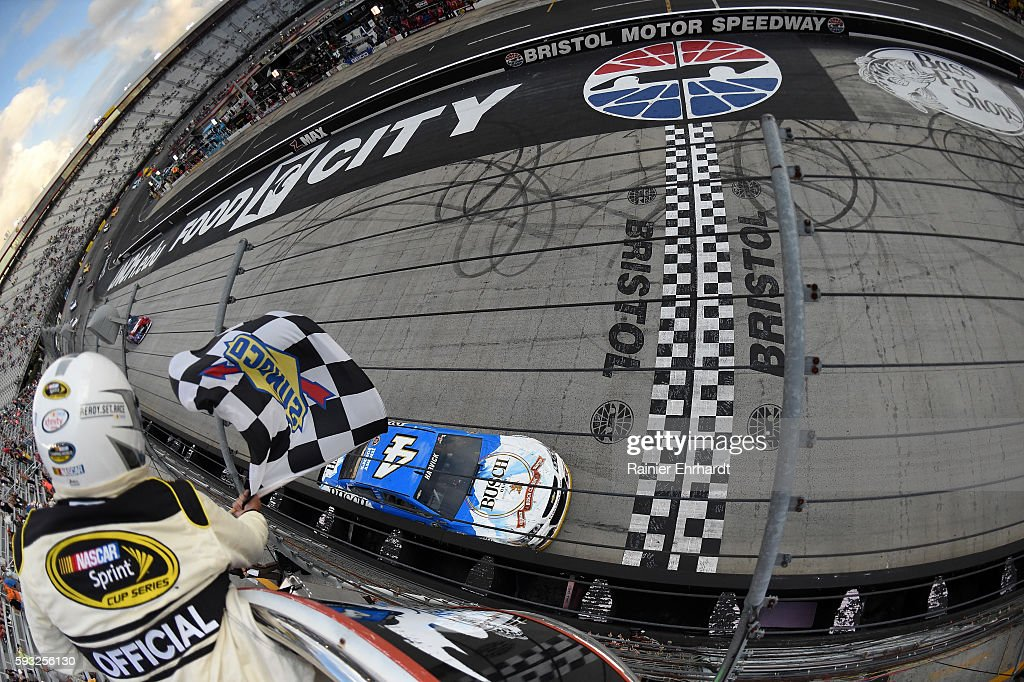 Kevin Harvick, driver of the #4 Busch Beer Chevrolet, takes the checkered flag to win the NASCAR Sprint Cup Series Bass Pro Shops NRA Night Race at Bristol Motor Speedway on August 21, 2016 in Bristol, Tennessee. The race was delayed due to inclement weather on Saturday, August 20.