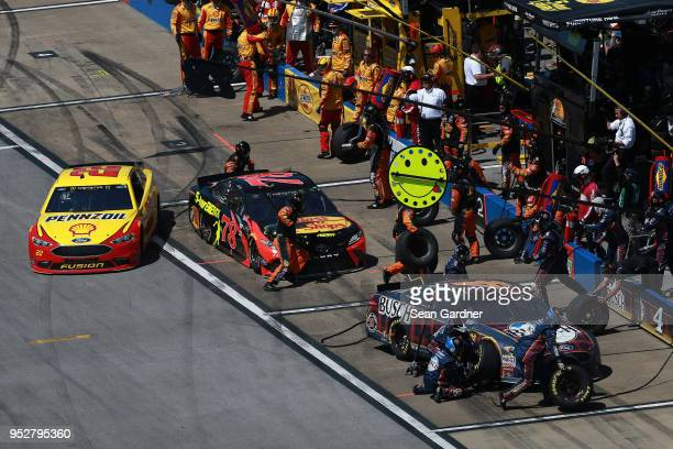 Kevin Harvick driver of the Busch Beer Flannel Ford Martin Truex Jr driver of the Bass Pro Shops/5hour ENERGY Toyota and Joey Logano driver of the...