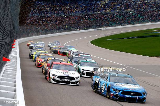 Kevin Harvick driver of the Busch Beer Ford leads a pack of cars during the Monster Energy NASCAR Cup Series Digital Ally 400 at Kansas Speedway on...