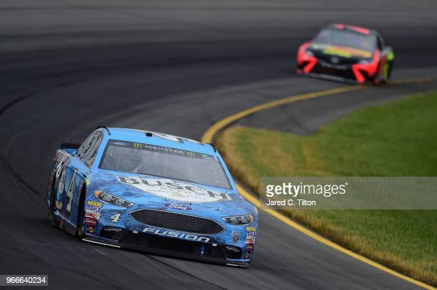 Kevin Harvick driver of the Busch Beer Ford leads Martin Truex Jr driver of the Bass Pro Shops/5hour ENERGY Toyota during the Monster Energy NASCAR...