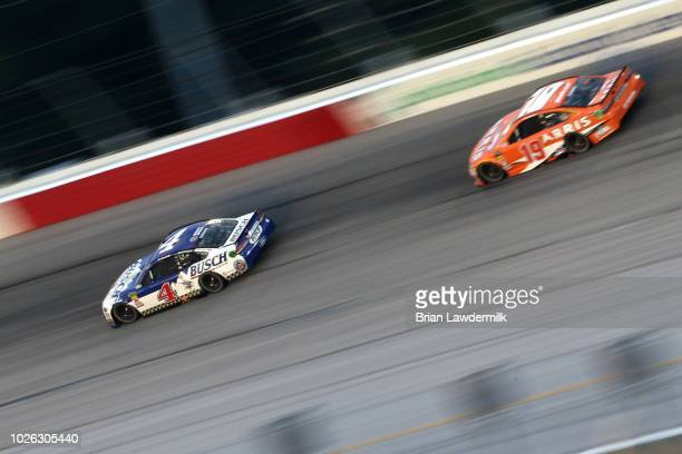 Kevin Harvick driver of the Busch Beer Throwback Ford leads Daniel Suarez driver of the ARRIS Toyota during the Monster Energy NASCAR Cup Series...