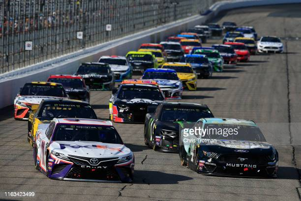 Kevin Harvick driver of the Busch Beer/National Forest Foundation Ford and Denny Hamlin driver of the FedEx Express Toyota lead the field during the...