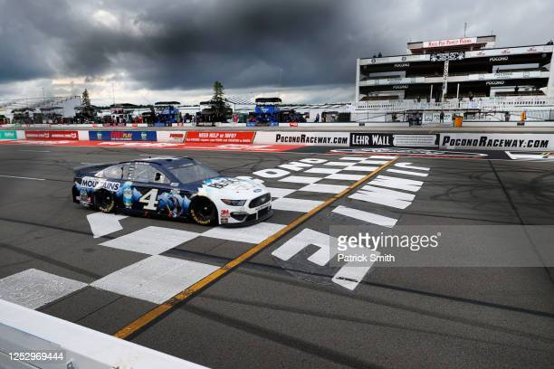 Kevin Harvick, driver of the Busch Head for the Mountains Ford, crosses the finish line to win the NASCAR Cup Series Pocono Organics 325 in...
