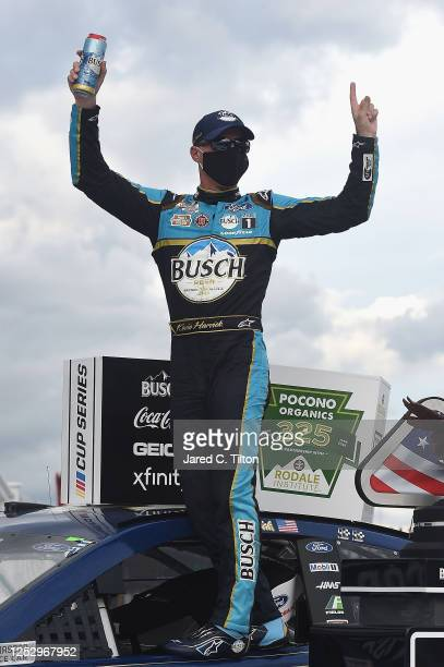 Kevin Harvick, driver of the Busch Head for the Mountains Ford, celebrates in Victory Lane after wining the NASCAR Cup Series Pocono Organics 325 in...