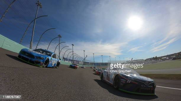 Kevin Harvick, driver of the Busch Light Ford, and Denny Hamlin, driver of the FedEx Express Toyota, lead a pace lap prior to the Monster Energy...