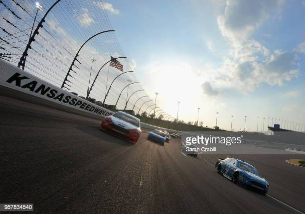 Kevin Harvick driver of the Busch Light Ford and Ryan Blaney driver of the REV Group Ford lead the field during a pace lap before the start of the...