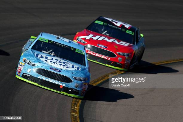 Kevin Harvick driver of the Busch Light Ford leads Kurt Busch driver of the Haas Automation/Monster Energy Ford during the Monster Energy NASCAR Cup...