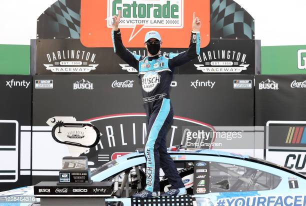 Kevin Harvick driver of the Busch Light YOURFACEHERE Ford celebrates in Victory Lane after winning the NASCAR Cup Series The Real Heroes 400 at...