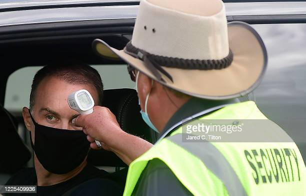 Kevin Harvick driver of the Busch Light YOURFACEHERE Ford has his temperature checked by NASCAR Security prior to the NASCAR Cup Series The Real...