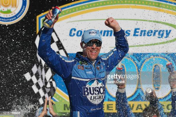 Kevin Harvick driver of the Busch Light/Mobil 1 Ford celebrates in Victory Lane after winning the Monster Energy NASCAR Cup Series Consmers Energy...