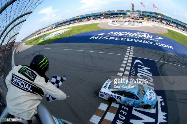 Kevin Harvick, driver of the Busch Light/Mobil 1 Ford, takes the checkered flag to win the Monster Energy NASCAR Cup Series Consmers Energy 400 at...