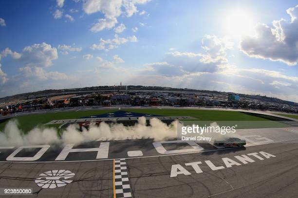 Kevin Harvick driver of the Hunt Brothers Pizza Ford celebrates with a burnout after winning the NASCAR Xfinity Series Rinnai 250 at Atlanta Motor...